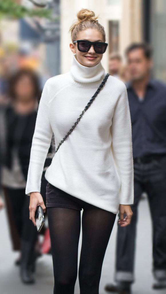 Gigi with white turtleneck and shorts on