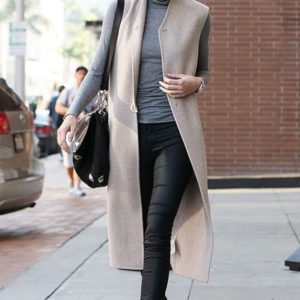 Kendall wears a tan long vest with turtlneck and dark pants