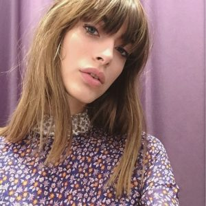 Louise Follain with bangs and a purple shirt