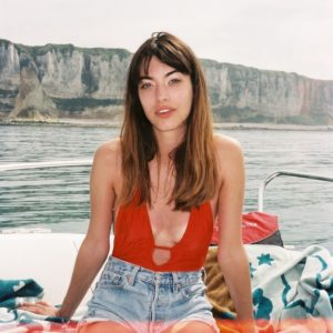 Louise in jean shorts and red top on a boat